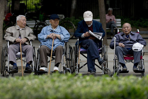 Chinese elderly men in wheelchairs with canes.