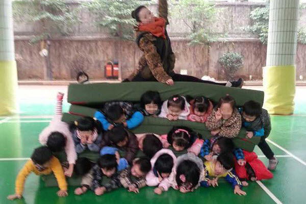 Parents stunned by photograph of Chinese kindergarten teacher sitting on a pile of children.