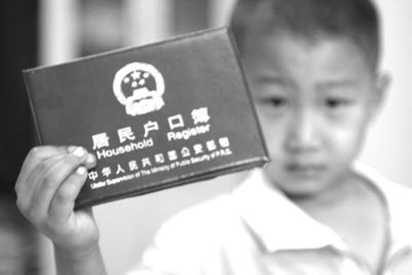 "A little Chinese boy holds up a ""hukou"" household registration booklet."