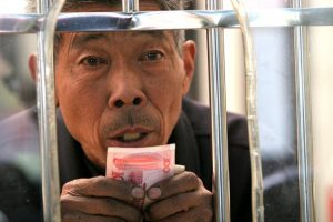 Elderly Chinese man holding 100 RMB bill preparing to purchase a train ticket.