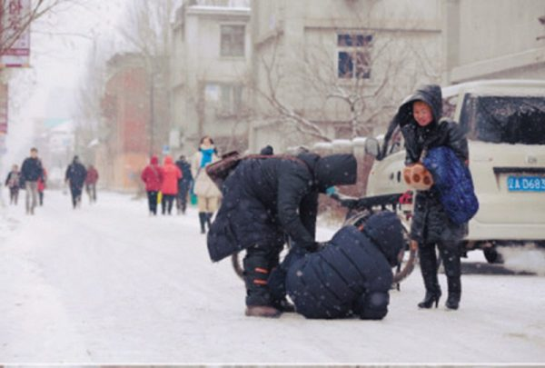 In Shenyang, a young Chinese man riding an electric bike helps and elderly man up after accidentally running into and knocking him down in the snow.