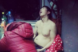 A topless Chinese man asleep on a train heading home from Hangzhou to Guiyang for Spring Festival 2014.