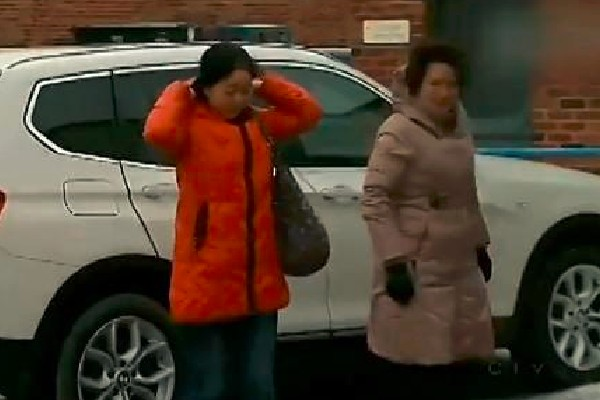 Two Chinese women are getting out of the expensive car.