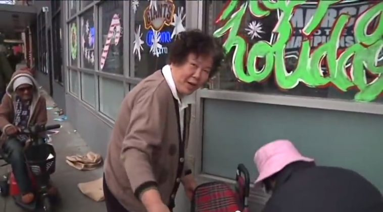 An elderly Asian woman in San Francisco taking donated goods to resell.