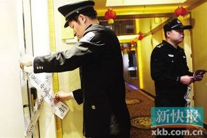 Chinese police officers in Dongguan, Guangdong province, seal up a room where prostitution was found.