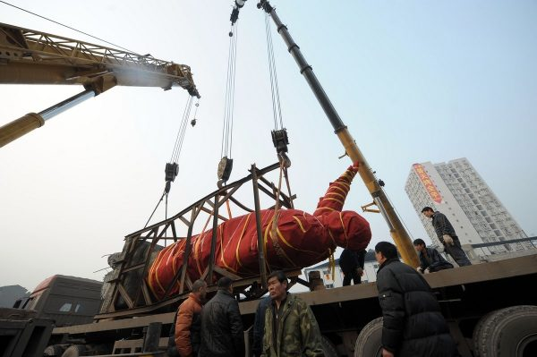 The Mao Zedong statue hoisted onto a flatbed trailer truck to be sent to the Chongqing City Industry Museum.