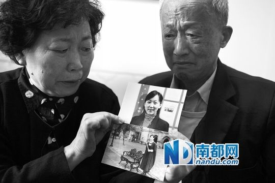 Liang Ya's parents are crying while holding their daughter's pictures.