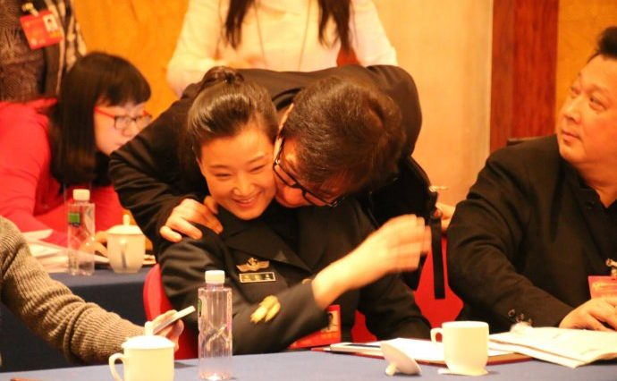 Jackie Chan cheek-to-cheek stealing a kiss from Song Zuying at the 2014 CPPCC meeting.
