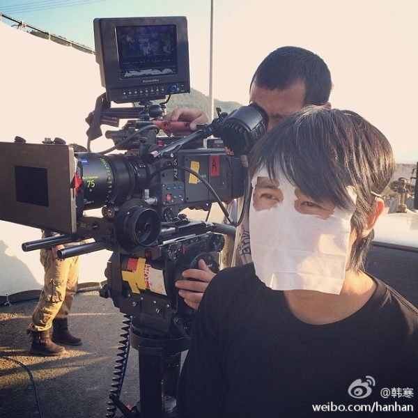Han Han with a napkin over his face attempting to even the tan on his face due to previously wearing sunglasses.