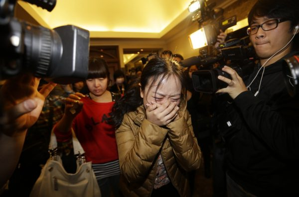 A relative of a passenger of Malaysia Airlines flight MH370 cries as she walks past journalists in Beijing