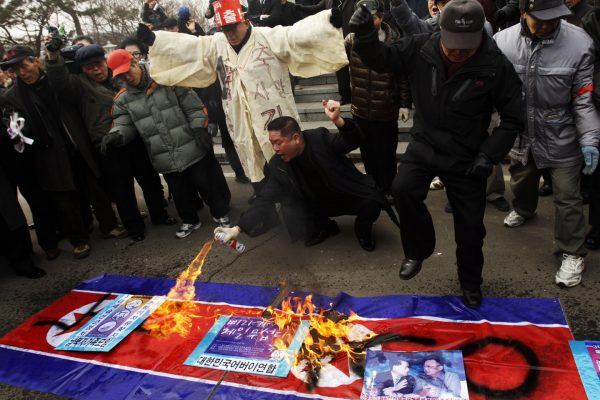 2011 February 16, on the birthday of Kim Jong-il, on the South Korean side of the Panmunjeom demilitarized zone, some North Korean refugees and South Korean people who support them burn the North Korean flag after releasing balloons carrying materials denouncing Kim Jong-un. REUTERS/Truth Leem