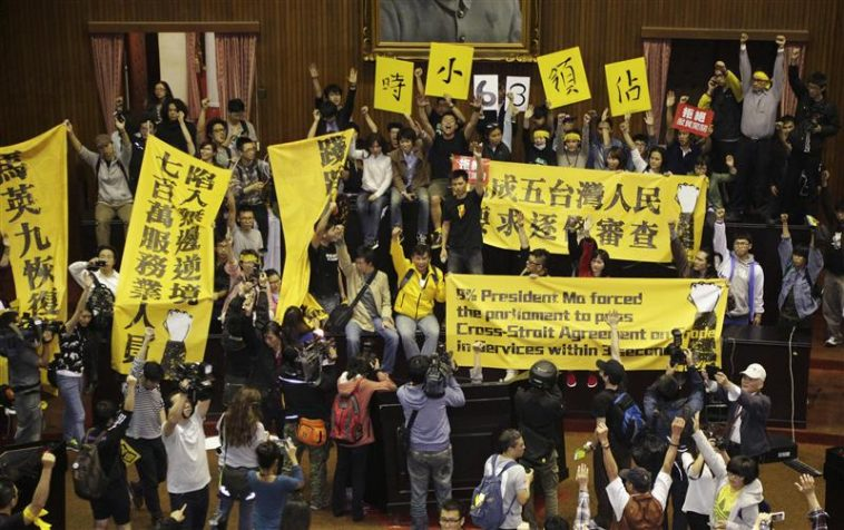 Students and other protesters hold banners inside Taiwan's legislature in Taipei, March 18, 2014. REUTERS/Stringer
