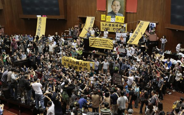 TAIPEI, TAIWAN - MARCH 19:  Students and protestors occupy the Taiwanese Parliament to protest against the act by the ruling Kuomintang party to ratify a controversial service and trade agreement with China on March 19, 2014 in Taipei, Taiwan. Over 200 students broke into the Taiwan Parliament and took over the main chamber in protest against the service and trade aggreement.  (Photo by Ashley Pon/Getty Images)