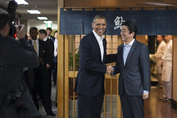 Obama is shaking hands with Japan's Prime Minister Shinzo Abe.