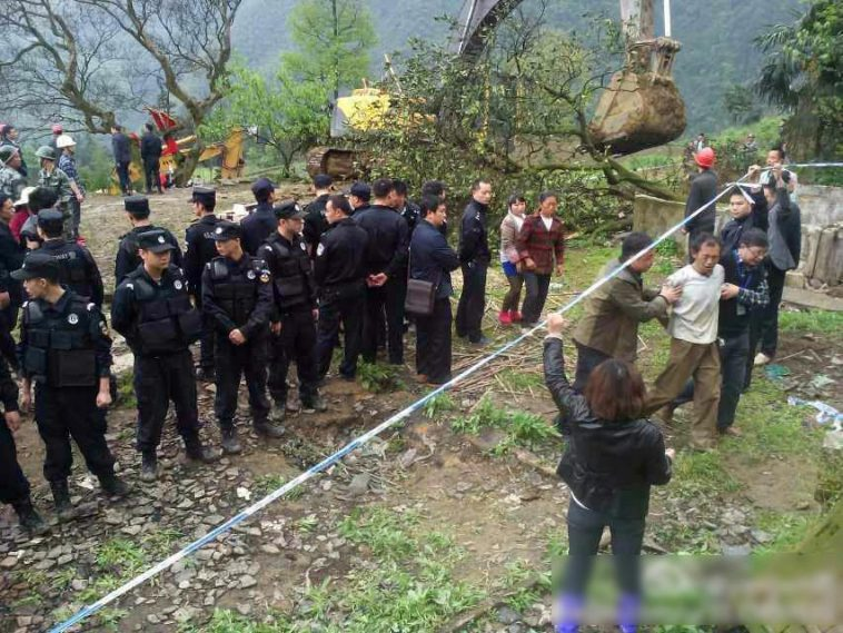 A villager is escorted away by police after an old 200-year-old tree is removed to make way for a highway in a Sichuan province village of China.