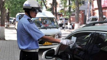 Chinese traffic police leaving a parking citation/ticket on the window of a car.