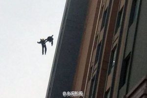 Two Chinese firefighters in Shanghai fall off the 13th floor of a building while responding to a residential building fire.