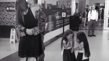 Two little girls giggle as a soldier kisses his wife after reuniting at the airport.