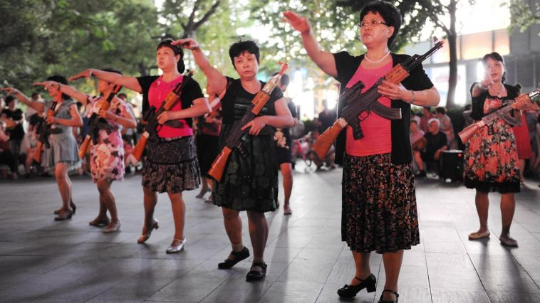 "Chinese ""aunties"" (older middle-aged women) carying toy AK-47 rifles plaza dancing and ""fighting Japanese devils"" on the streets of Beijing."