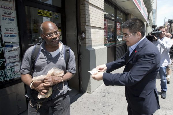 Chinese billionaire philanthropist Chen Guangbiao handing out $100 bills to poor Americans in New York.