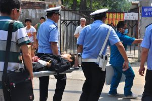 Police taking a Chinese man to a hospital after he was found having slit his wrist by a river trying to commit suicide over ongoing housing worries.