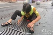 An elderly Chinese woman over 60 years old in Nanjing, China who works all year as a sanitation worker, sitting on the ground fishing out littered cigarette butts from a drain gutter.