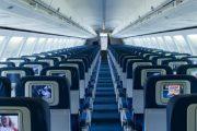 Airplane cabin aisle with seatbacks.