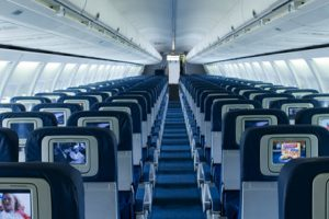 Airplane cabin aisle with seatbacks.