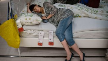 A Chinese woman sleeping on a display bed at an IKEA in Beijing.