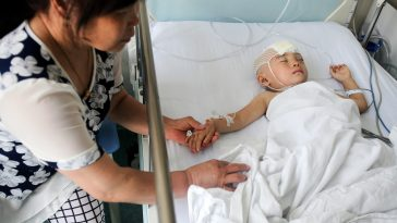 A 3-year-old girl lies in the hospital with a fractured skull after her home was invaded by a group of men sent to intimidate them into selling their house in Xi'an, China.