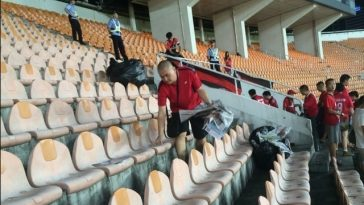 Chinese Guangzhou Evergrande FC football fans clean up litter and garbage after a match.