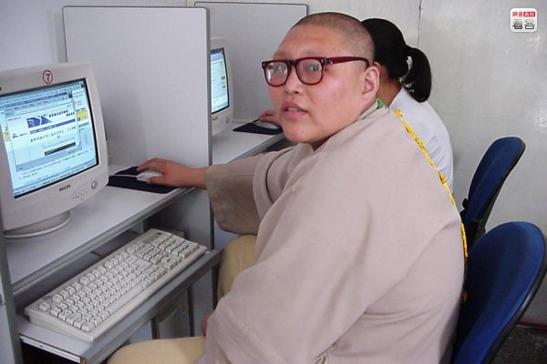A Chinese monk using a computer.