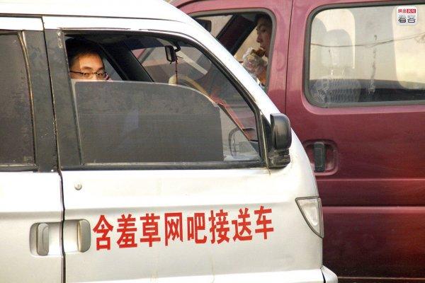 Internet bar shuttles wait outside school gates in China.