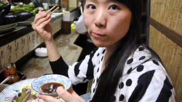 A Japanese woman eating fresh raw frog sashimi (sushi) in Japan.