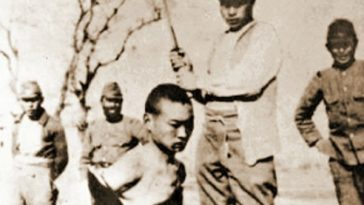 An Imperial Japanese soldier prepares to cut off a Chinese person's head with a katana in World War II.