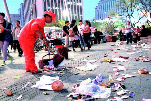 A sanitation worker in China sweeping up litter.