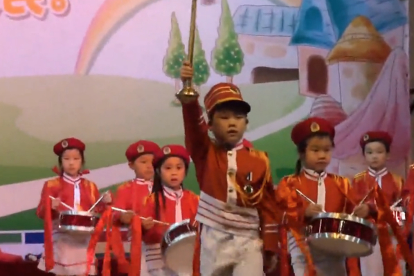 Chinese children on stage marching to a Japanese military song at an international kindergarten in Shanghai.