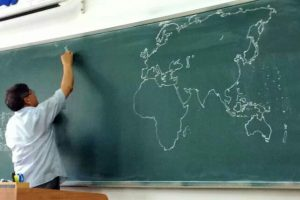 Chinese teacher freehand draws world map on chalkboard in class.