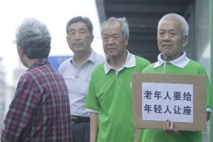 "Elderly men holding a sign saying ""The old should give up seats to the young""."