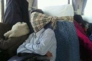 "A Chinese train passenger using a ""Burberry"" scarf tied around the back of his seat to keep his head up while sleeping."