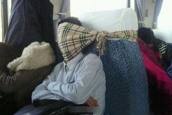 """A Chinese train passenger using a """"Burberry"""" scarf tied around the back of his seat to keep his head up while sleeping."""