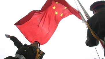 A Chinese soldier unfurls the red, five-starred national flag of the People's Republic of China at the raising ceremony in Beijing on 2014 October 1, celebrating the country's 65th anniversary since its founding.