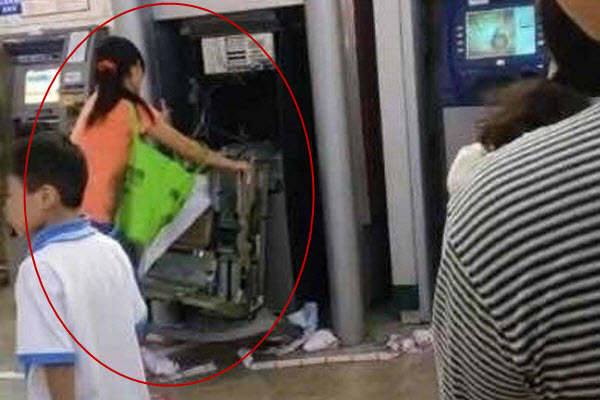 A Chinese woman in Dongguan tears apart an ATM machine that swallowed her bank card.