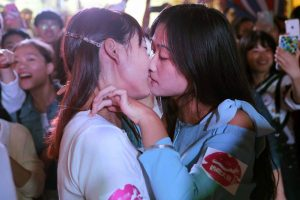 Two Chinese girls kissing each other in Jinhua, Zhejiang province, for a competition to win an Apple iPhone6.