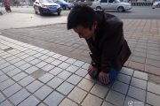 A young Chinese man on his knees begging his girlfriend to forgive him.