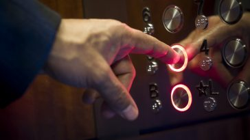A hand/finger pressing an elevator button.