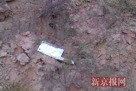 A photo provided by an insider shows a large bloodstain on a muddy patch of ground. In the blood stain is a stainless steel kitchen knife. Source: Beijing News