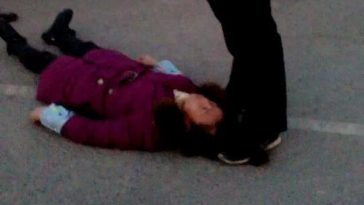 A Chinese police officer captured stepping on a female migrant workers' hair, holding her to the ground.