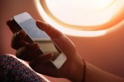 A woman's hand holds a white Apple iPhone next to an airplane window.