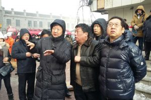 Shi Jiaxing [right] at the scene of the fire rescue wearing an expensive name brand down padded jacket, inciting the ire of netizens.